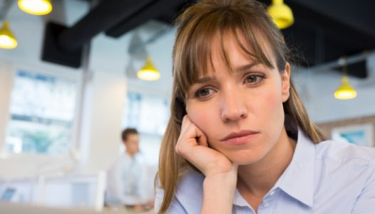 Depressed businesswoman in office behind her laptop